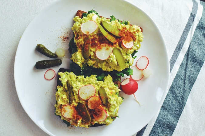 picture of an open faced egg salad sandwich garnished with cornichons and radishes