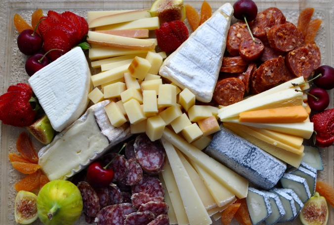 Plate of cheeses with fresh figs and cherries