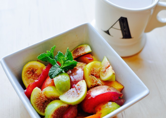 Bright bowl of fruit salad with figs, plums, and nectarines