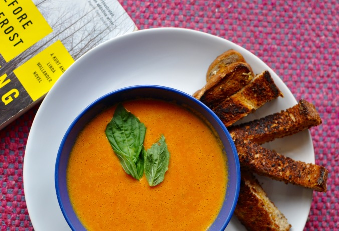 Bowl of sweet bell pepper soup in blue bowl with grilled cheese sticks