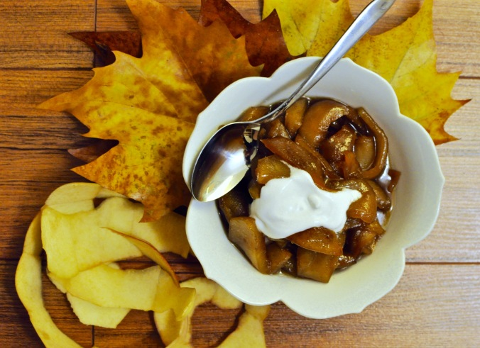 Bowl of cooked apples with coconut milk, maple leaves, and apple peel.