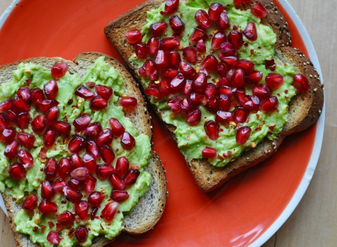 Toast on an orange plate topped with avocado, pomegranate seeds, and red chillies.