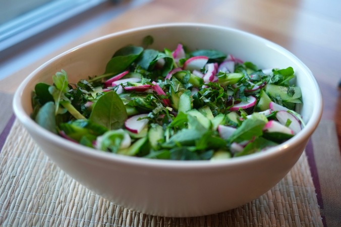 Big green tossed salad in an oval bowl with radishes and red onion