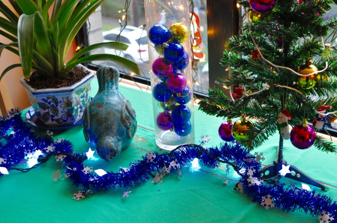 Close up of bird decorations and Christmas tree on a kitchen table with lights.