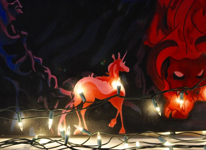 Close up of Christmas lights with the Last Unicorn painting in background.