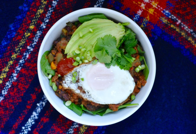 Vegetarian slow cooker chili in a shallow white bowl. The chili is topped with an egg, sliced avocado, and scallions.