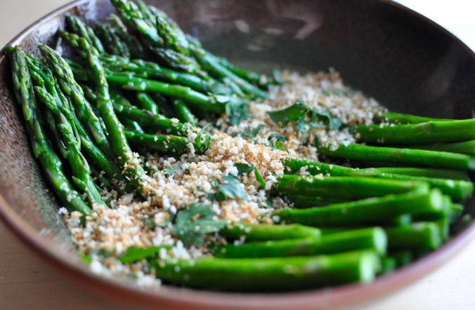 Earthenware shallow bowl with roasted asparagus, toasted breadcrumbs, and parsley.