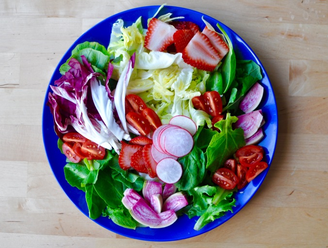 Large blue plate full of salad with iceberg lettuce, baby kale, radishes, tomatoes, and strawberries.