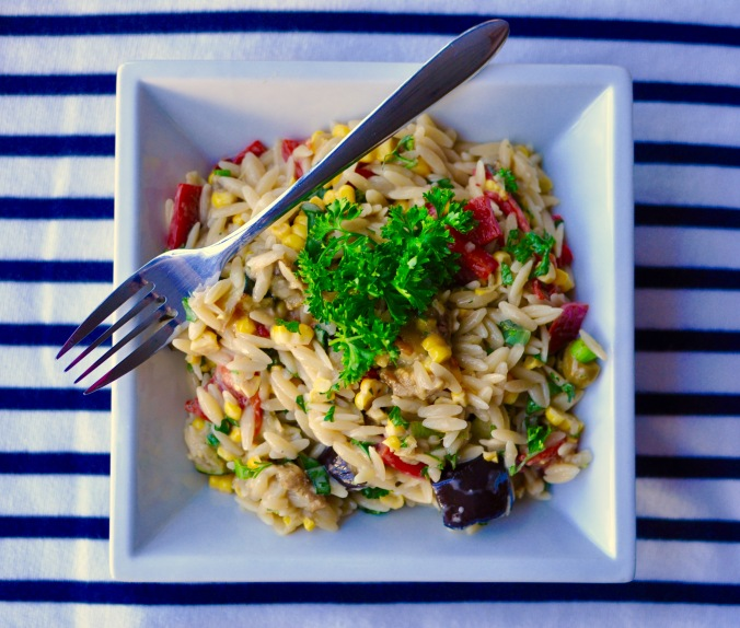 Square white bowl with creamy orzo pasta salad with roasted red peppers, zucchini, and eggplant. On a blue and white striped tablecloth.