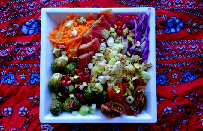A white square plate full of mixed raw and roasted vegetables on an orange and blue background.
