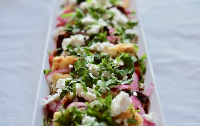 Halloumi Salad with Roasted Red and Jalapeño Peppers, Pickled Red Onions, and Mint in a narrow white serving dish on a white tablecloth.