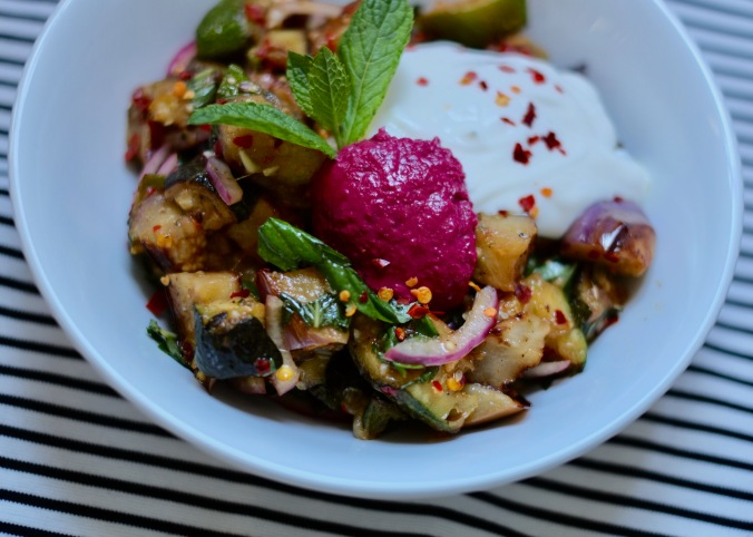 Cooked eggplant and zucchini salad topped with beetroot hummus, Greek yogurt and chilies. The salad is in a large white bowl, garnished with a sprig of mint, and laid out on a black and white striped tablecloth.