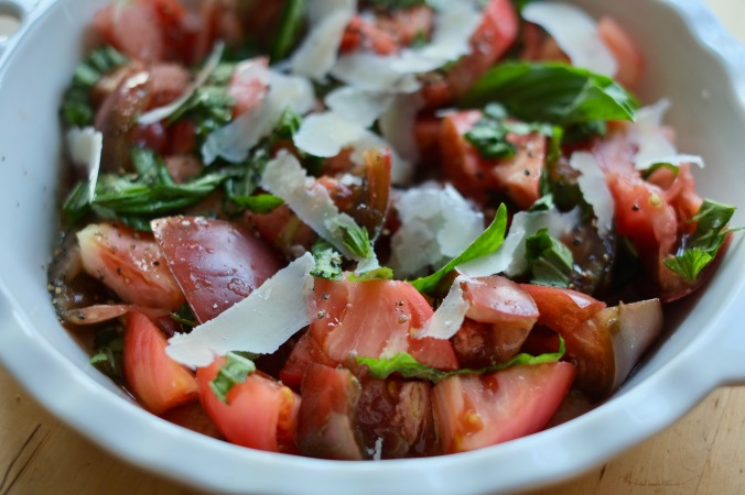 Composed summer tomato salad with fresh basil and shaved parmesan in a white shallow bowl.
